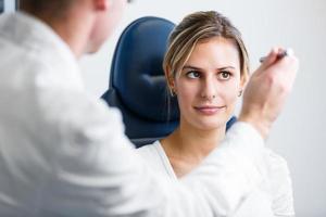 ganska ung kvinna som har ögonen undersökt med optometrik foto