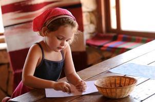 liten flicka sitter vid bordet färgläggning med kritor foto