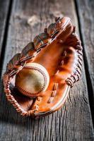 närbild av gammal baseballhandske och boll foto
