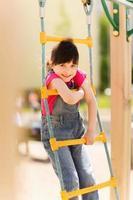 glad liten flicka som klättrar på lekplatsen