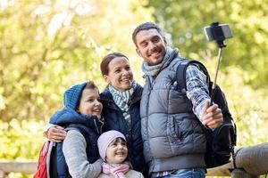lycklig familj med smartphone-selfie-pinne i skogen foto