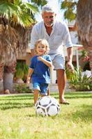 farfar som spelar fotboll med barnbarnet i trädgården foto