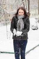glad kvinna formar en snöbal foto