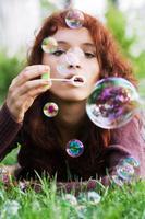 ung kvinna blåser bubblor foto