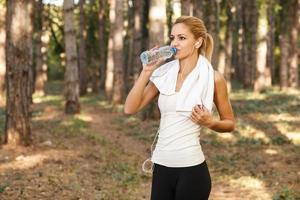 vackra unga kvinnor som dricker vatten efter att ha kört foto