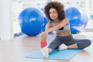 sportig kvinna som sträcker händerna till benet i fitnessstudio foto