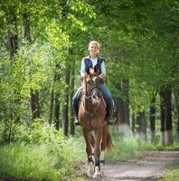 ung kvinna som rider på en häst foto