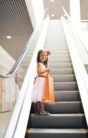glad liten flicka med shoppingväska i gallerian