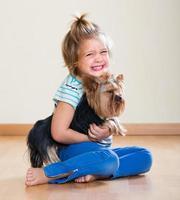 söt liten flicka med yorkshire terrier inomhus foto