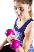 fit kvinna lyfter rosa hantel foto