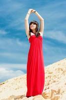 flicka i en röd klänning poserar på en sanddyn