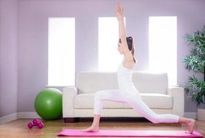 fit kvinna som gör yoga på matta foto