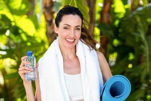 leende brunett innehav flaska vatten och träningsmatta foto