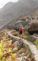 kondition. ung kvinna kör på en bergsväg foto