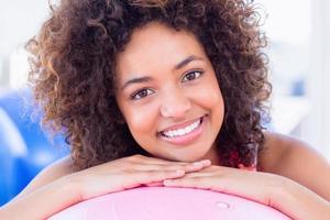 porträtt av en fit leende ung kvinna med fitness boll foto