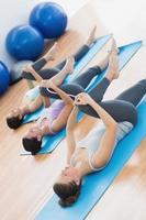 sportiga människor som sträcker ben i fitnessstudio foto