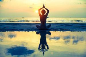 yogakvinna som sitter i lotus poserar på stranden foto