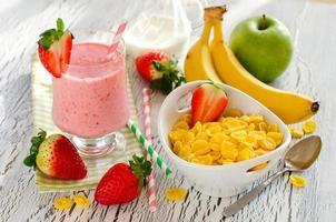 hälsosam frukost med cornflakes, jordgubbsmoothie och frukt foto