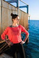 charmig kvinna tar paus efter träning på stranden foto