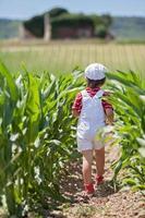 söt pojke med vit hatt och overaller, innehar vallmo foto