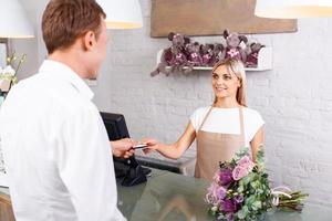 trevlig blomsterhandlare som serverar kund foto