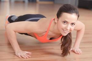 trevlig kvinna som gör armhävningar i gymmet foto
