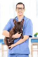 ung manlig veterinär i uniform som håller en hund inomhus foto