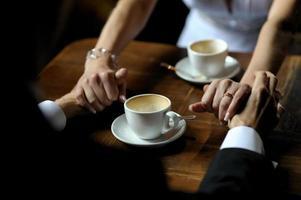 bruden och brudgummen som håller varandras händer foto