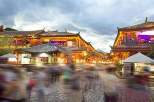 lijiang gamla stad på kvällen med tråkig turist. foto
