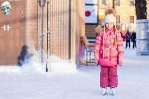 bedårande glad liten flicka som tycker om åka skridskor på isbanan