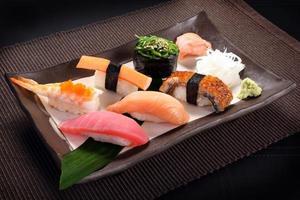 blandad sushisats med wasabi på keramisk maträtt foto