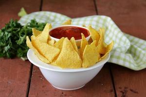 majs tortillachips i en skål med tomatsås foto