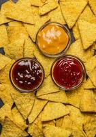 majs tortilla chips bakgrund med doppar olika, ovanifrån, foto