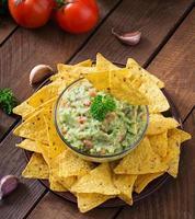 guacamole avokado, lime, tomat, lök och koriander, serveras med nachos foto