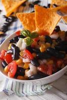 mexikansk salsa med bönor och majs chips nachos närbild. vertikal foto