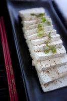 tofu på den svarta plattan foto