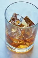 whisky med is på ett bord foto