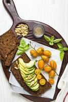 gula körsbärstomater och avokado med pinjenötter. basilikablad. foto