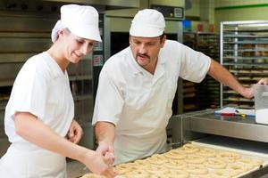 kvinnliga och manliga bagare i bageriet foto