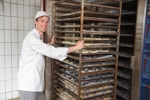 bagaren skjuter rack full av bröd in i ugnen foto
