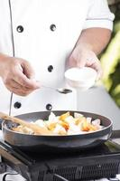 kock som sätter kryddasås i pannan foto