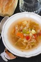 grönsakssoppa med bröd och vatten foto