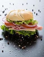 skinkasmörgås på svart bord foto