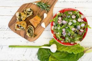 schweiziska chard rullar på skärbräda med sallad raket rädisor foto