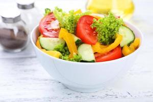 färsk grönsakssallad på vit träbakgrund