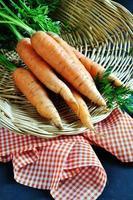 färska organiska morötter, rustik bakgrund, selektiv inriktning foto
