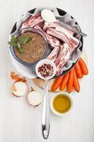 matlagningsingredienser i stekpanna: råa revben, gröna linser, morötter, foto