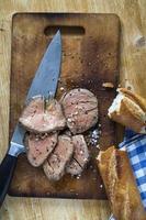 stekt nötkött på skärbräda med salt och peppar foto