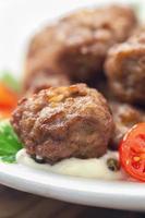 köttbullar med sås och färska tomater foto