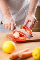 man skär paprika i köket foto